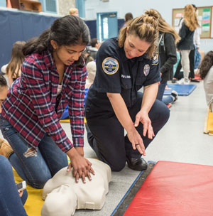 EMS Officer Teaching a Young Woman CPR