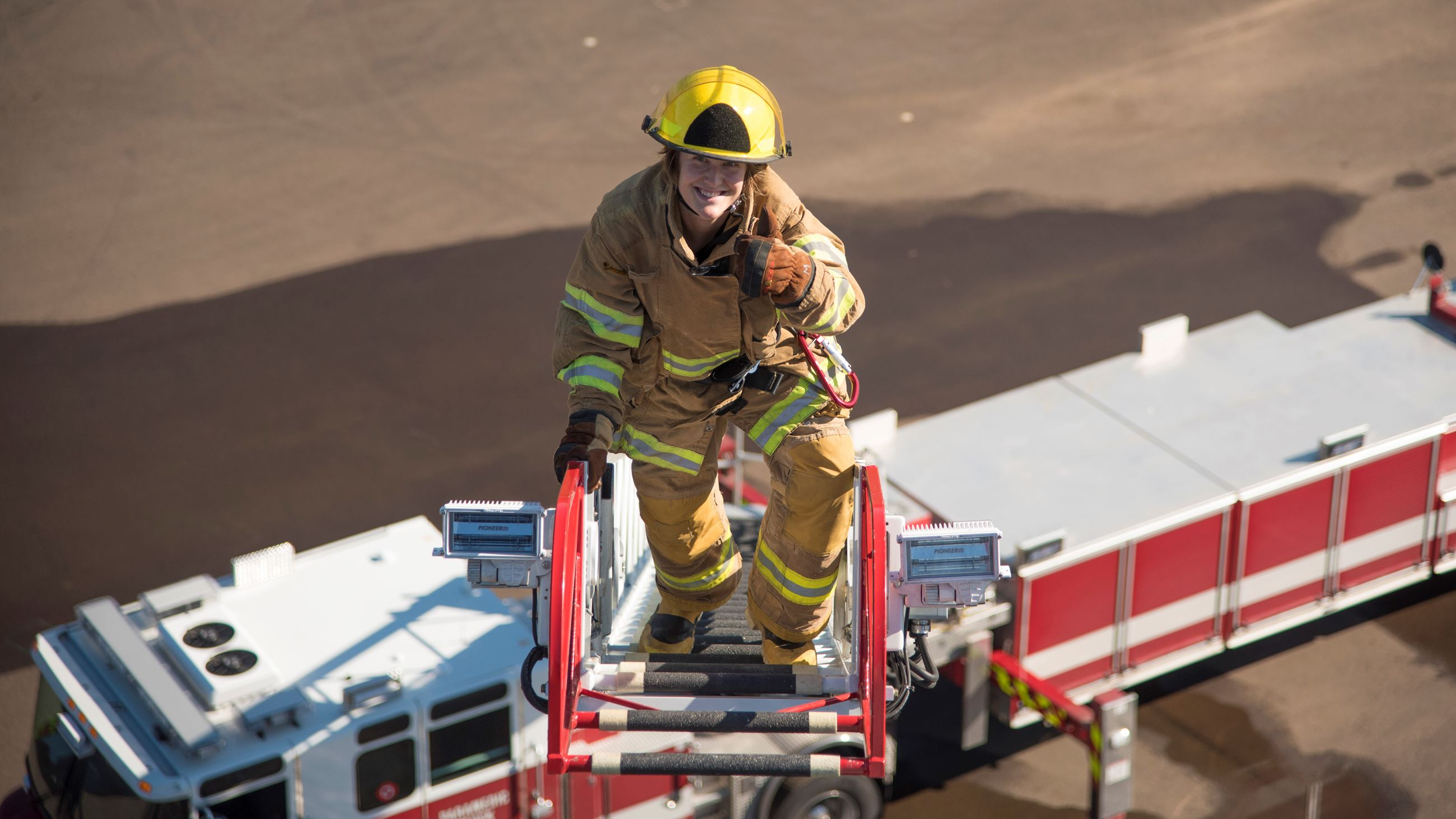Career Day participant climbing up ladder on truck