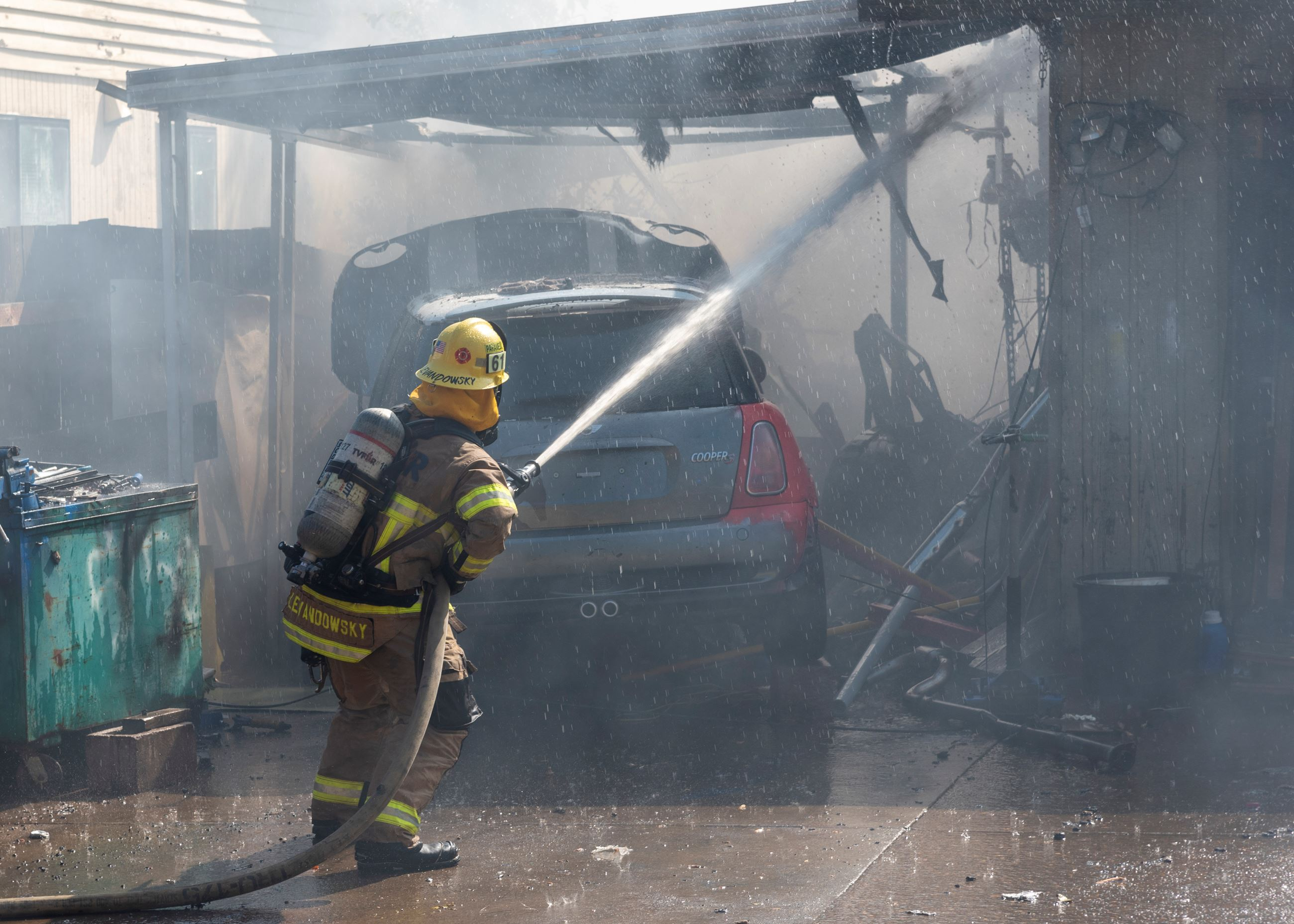 Firefighter sprays water on residential fire