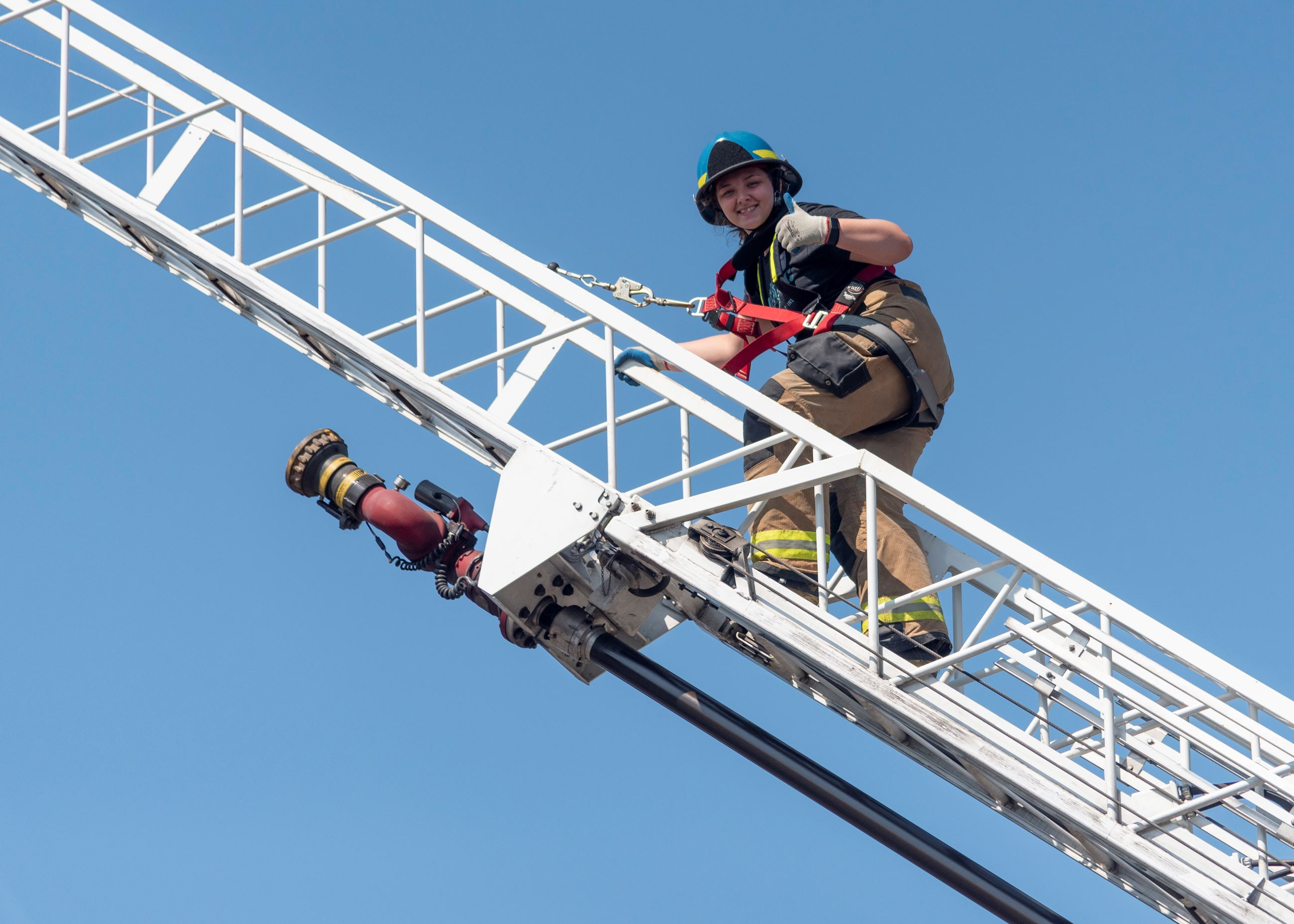 Portland Metro Fire Camp participant on extended truck ladder gives thumb's up