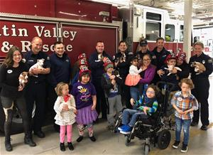 Firefighters with kids and Pile of Pups